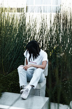 a person sitting outdoors in front of tall grasses