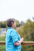 an elderly woman looking over a railing thinking