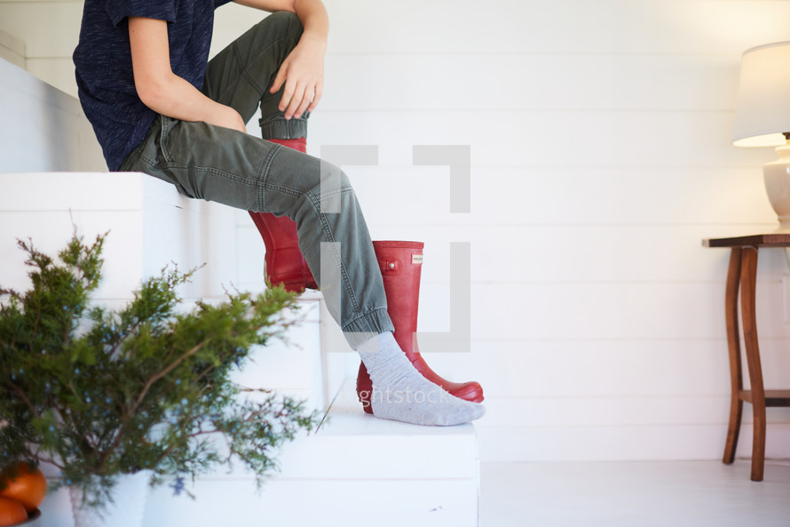 kid putting on red rain boots