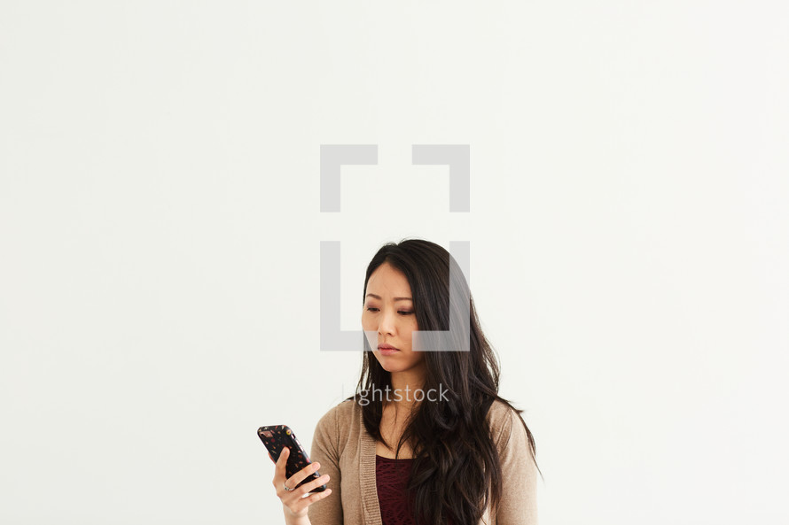 an upset woman looking at a cellphone screen