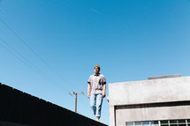 man walking on the edge of a roof