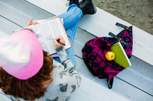 Teenage girl reading bible,  1 Timothy 4:12,  bleachers, youth, student, study, devotional, backpack, notebook