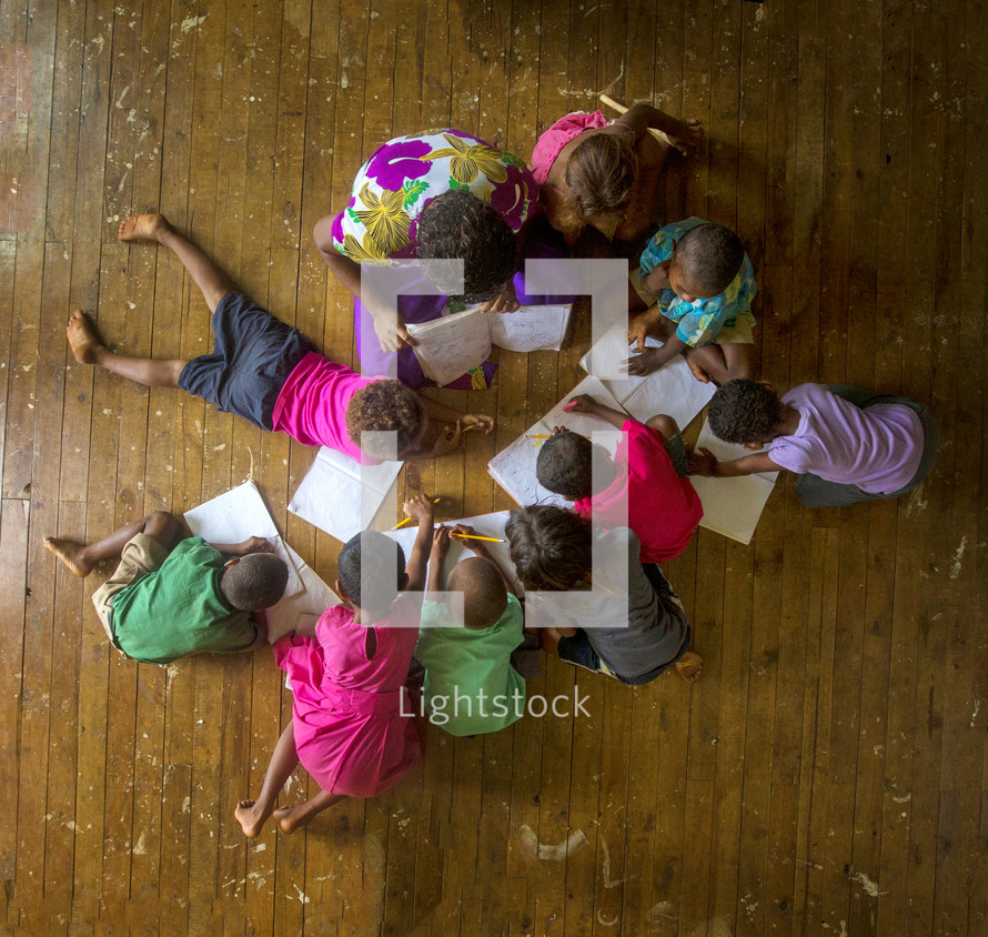 Children circled together reading and writing