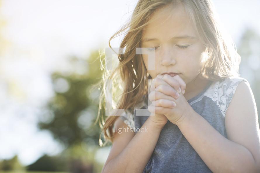 Little girl in prayer outside with sun shining.