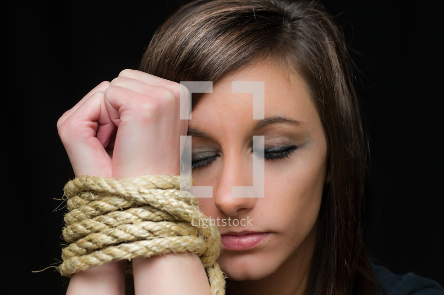 Woman with her wrists bound by rope.