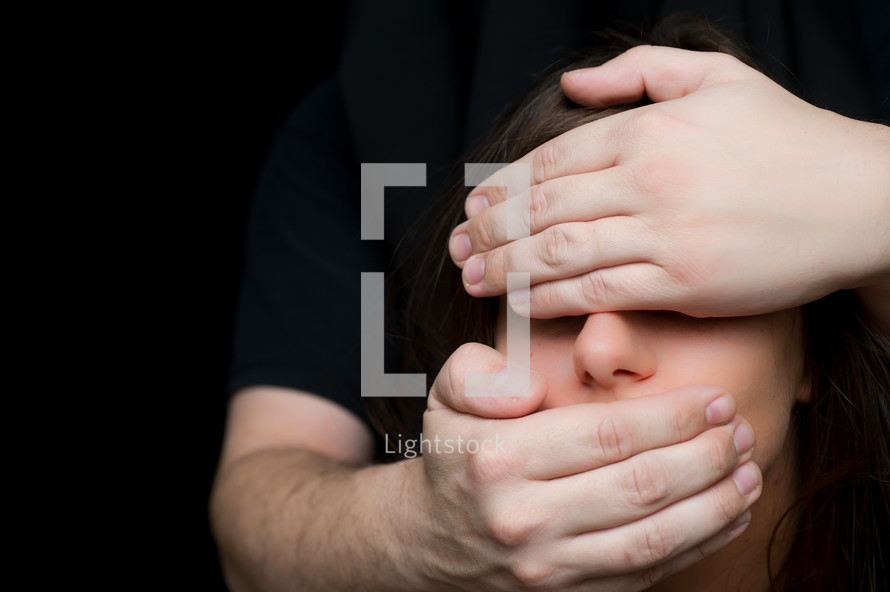 See no evil; speak no evil. A woman with her mouth and ear covered by a man's hands.