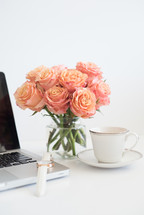A laptop computer, white wristwatch, coffee cup and saucer and vase of peach roses on a white surface.