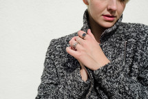 a female model in a sweater clasping her hands