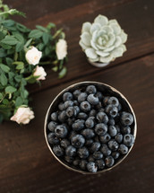 bowl of blueberries, roses, succulent plant