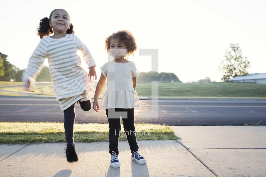 sisters dancing on a sidewalk