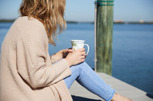 a woman with a coffee cup sitting on a pier