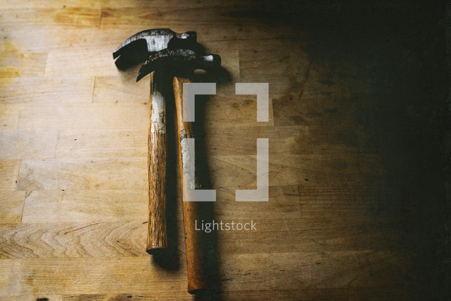 two hammers on a wood workbench