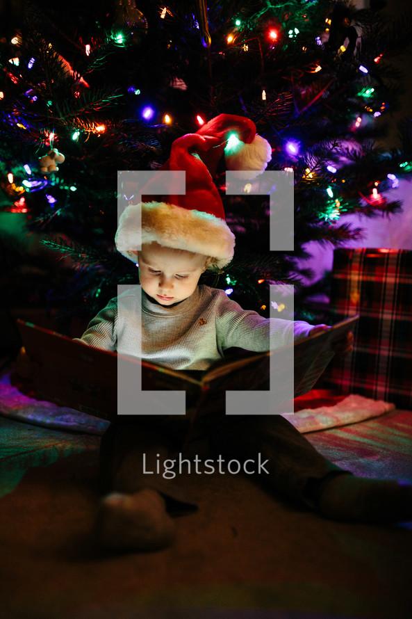 a boy reading a book under a Christmas tree