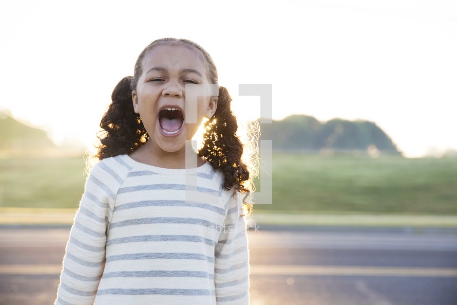 a toddler girl in pigtails yelling