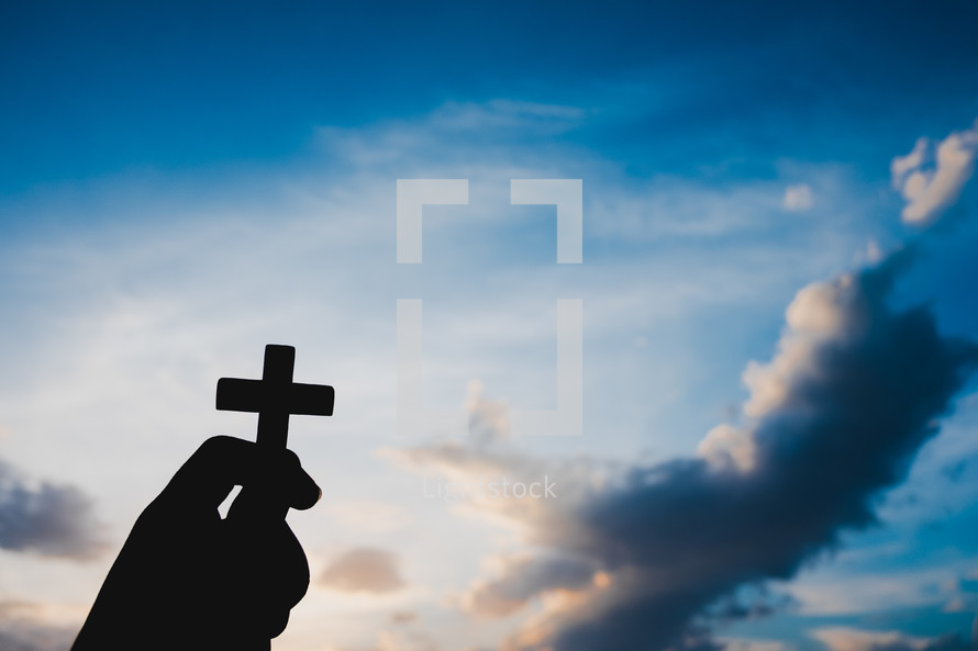 silhouette of a hand holding up a small cross