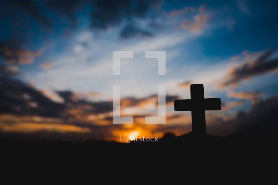 silhouette of a hand holding up a small cross at sunset