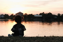 child sitting by a pond at sunset