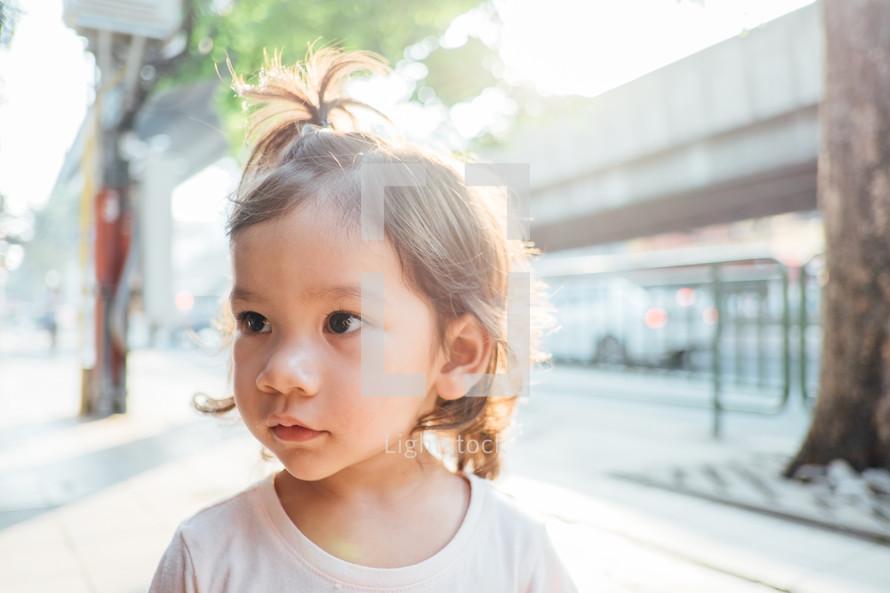 face of a little girl standing on a sidewalk