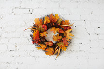 fall wreath on a white brick wall