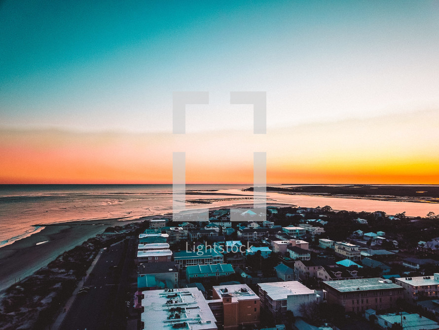 aerial view over a coastal town at sunset