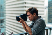 A man looks through a video camera.