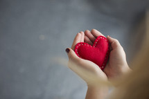 woman holding a red felt heart