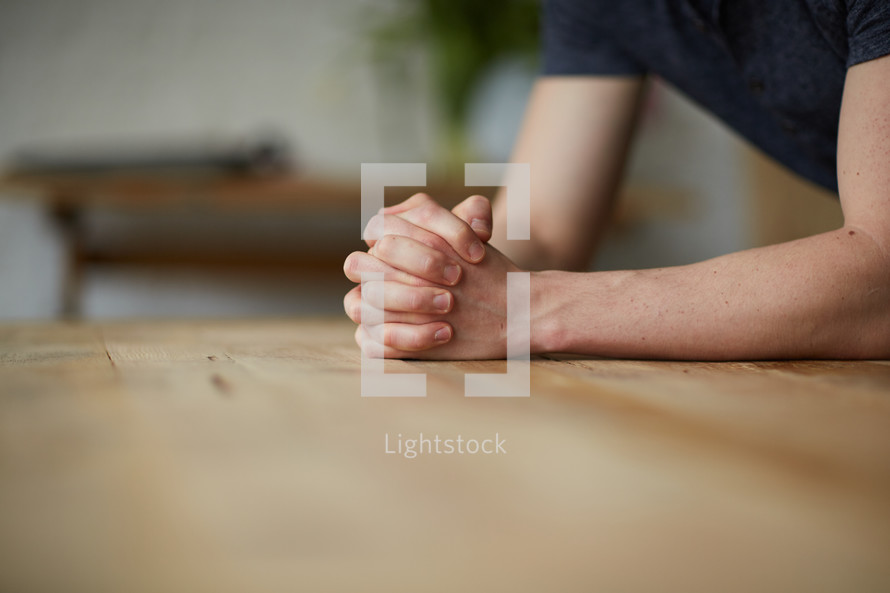 praying hands on a wood table