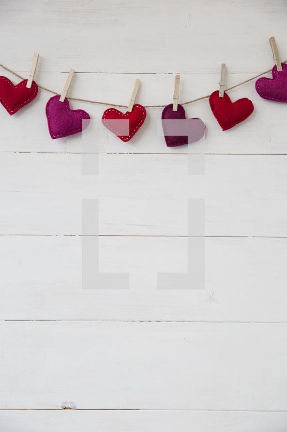 felt hearts hanging on a clothesline.