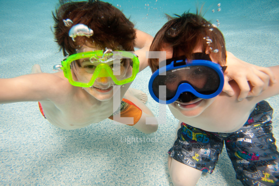 boys wearing goggles under the water