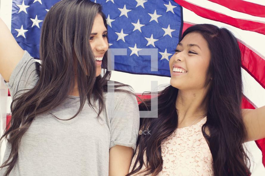 friendship between young women under an American Flag