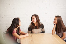 mother and daughters talking around a table