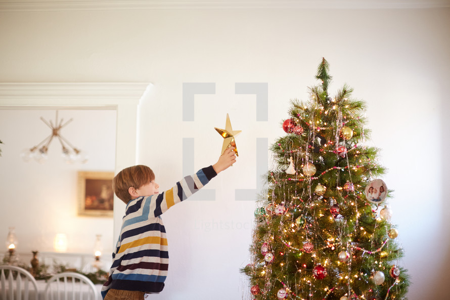 young kid reaching to put a star on the Christmas tree