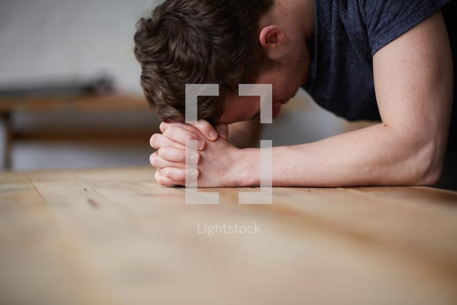 a man with his head on praying hands