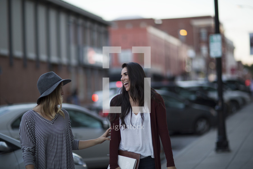 friends walking down a sidewalk carrying Bibles