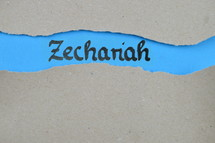 Zechariah - torn open kraft paper over blue paper with the name of the prophetic book Zechariah