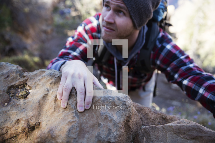 hand reaching to grab holding of a rock