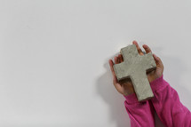 girl holding a stone cross