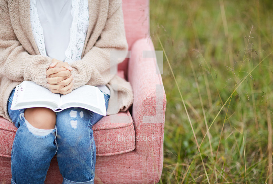 a woman sitting in a chair with praying hands over a Bible