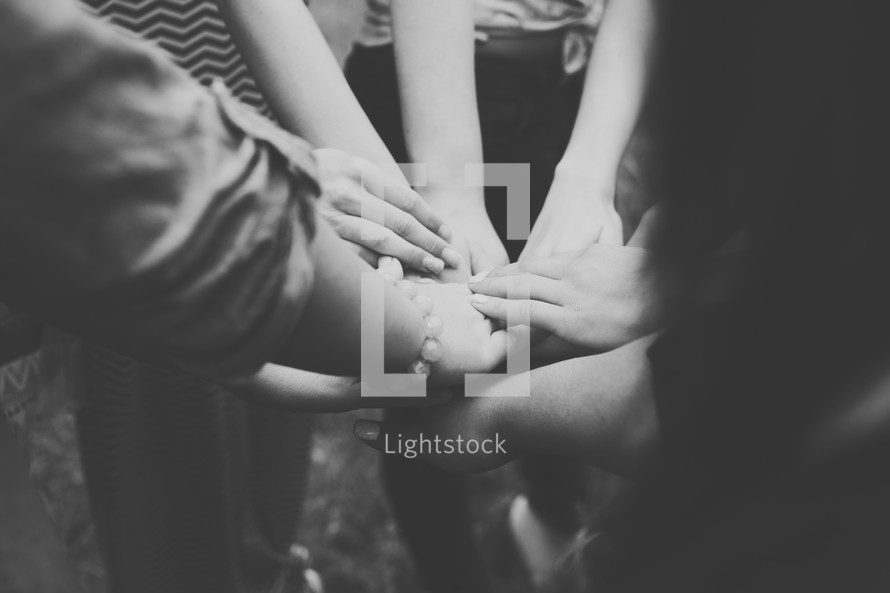 A group of girls are united as they put their hands together.