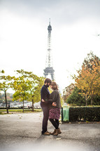 a couple standing in front of the Eiffel Tower