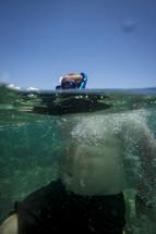 Snorkeler with head above water in ocean.