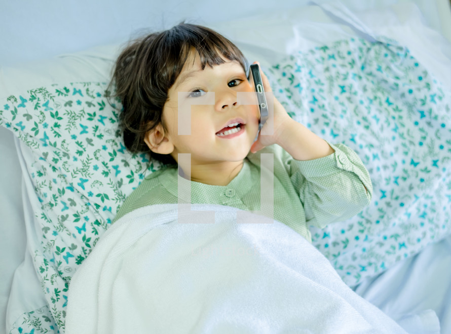 toddler girl talking on a cellphone in bed