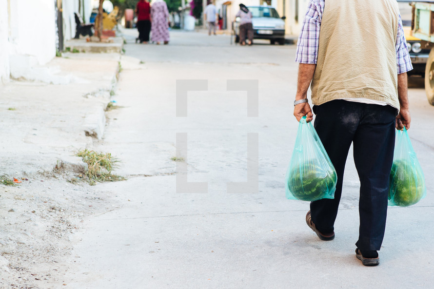 a man walking carrying bags of watermelons