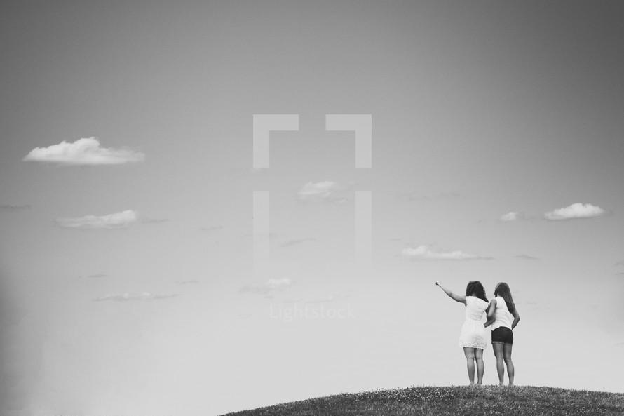 Girlfriends standing on a hill.
