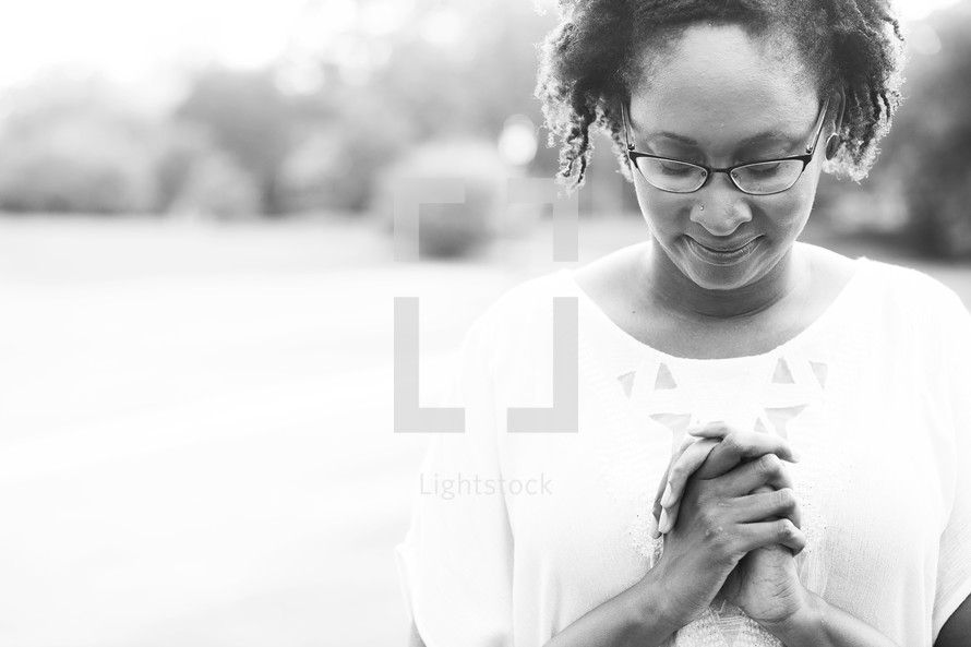 African-American woman with praying hands outdoors