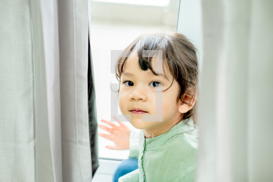 little standing at a window