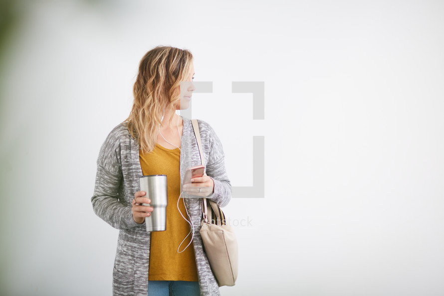 a woman standing holding a purse and listening to earbuds