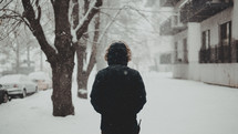 a man in a winter coat standing outdoors in snow