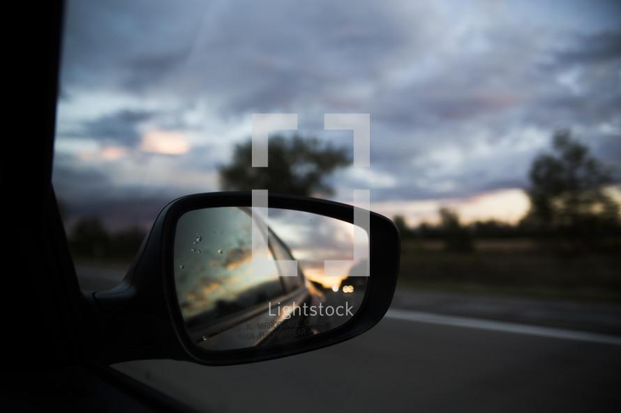 rain on car mirror at sunset
