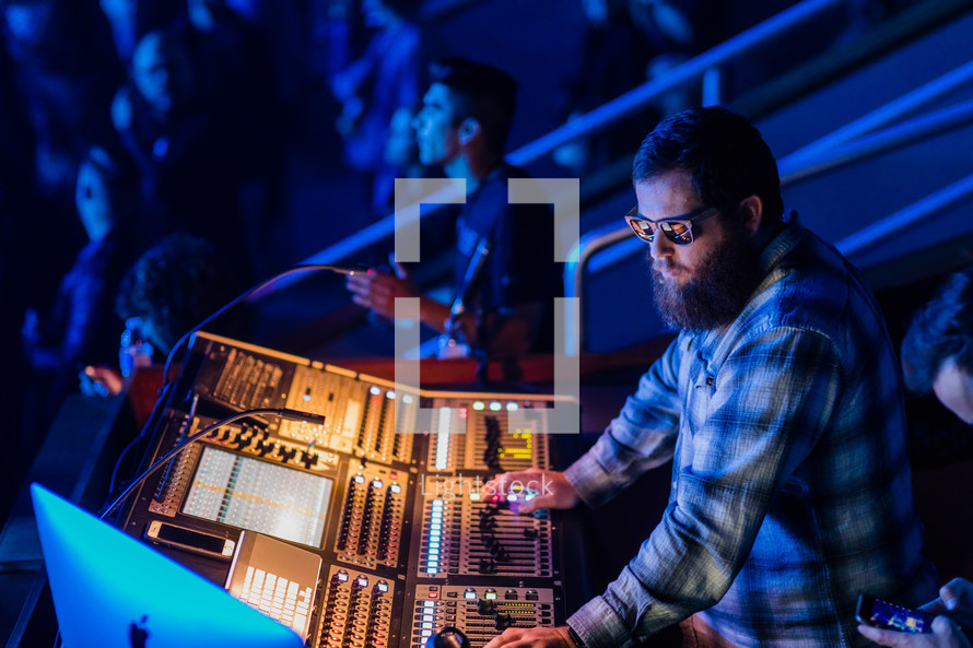 a man behind a soundboard at a youth conference concert